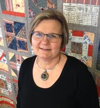 Photograph of Jane Peterson, upper torso and head standing in front of the MPC quilt.