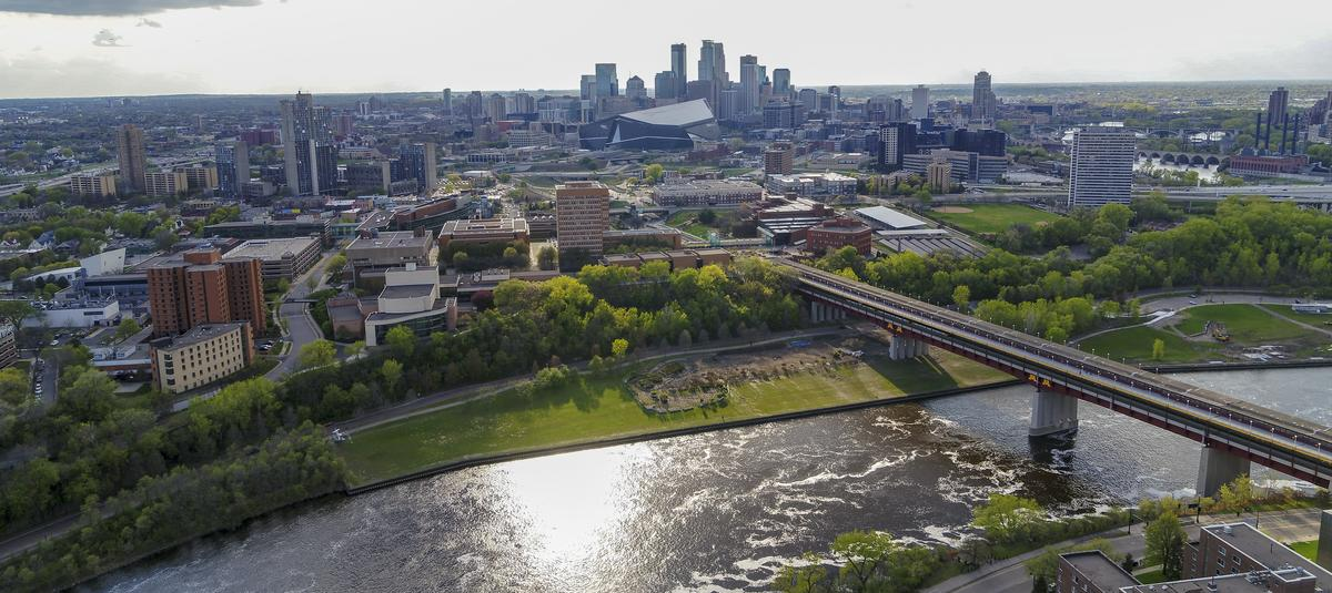 Aerial Photograph of the Mississippi River, the Washington Ave Bridge, and West Bank with Cedar Riverside and downtown Minneapolis in the distance.