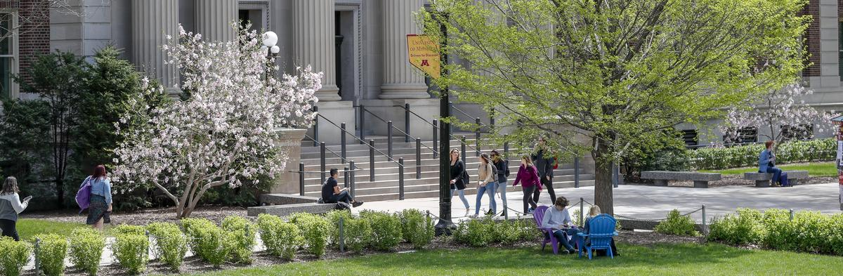 Stock photograph of students walking around in a plant filled area on campus in spring.