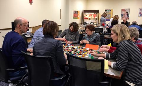 Photograph of a group of people sitting at a table building something out of building blocks.